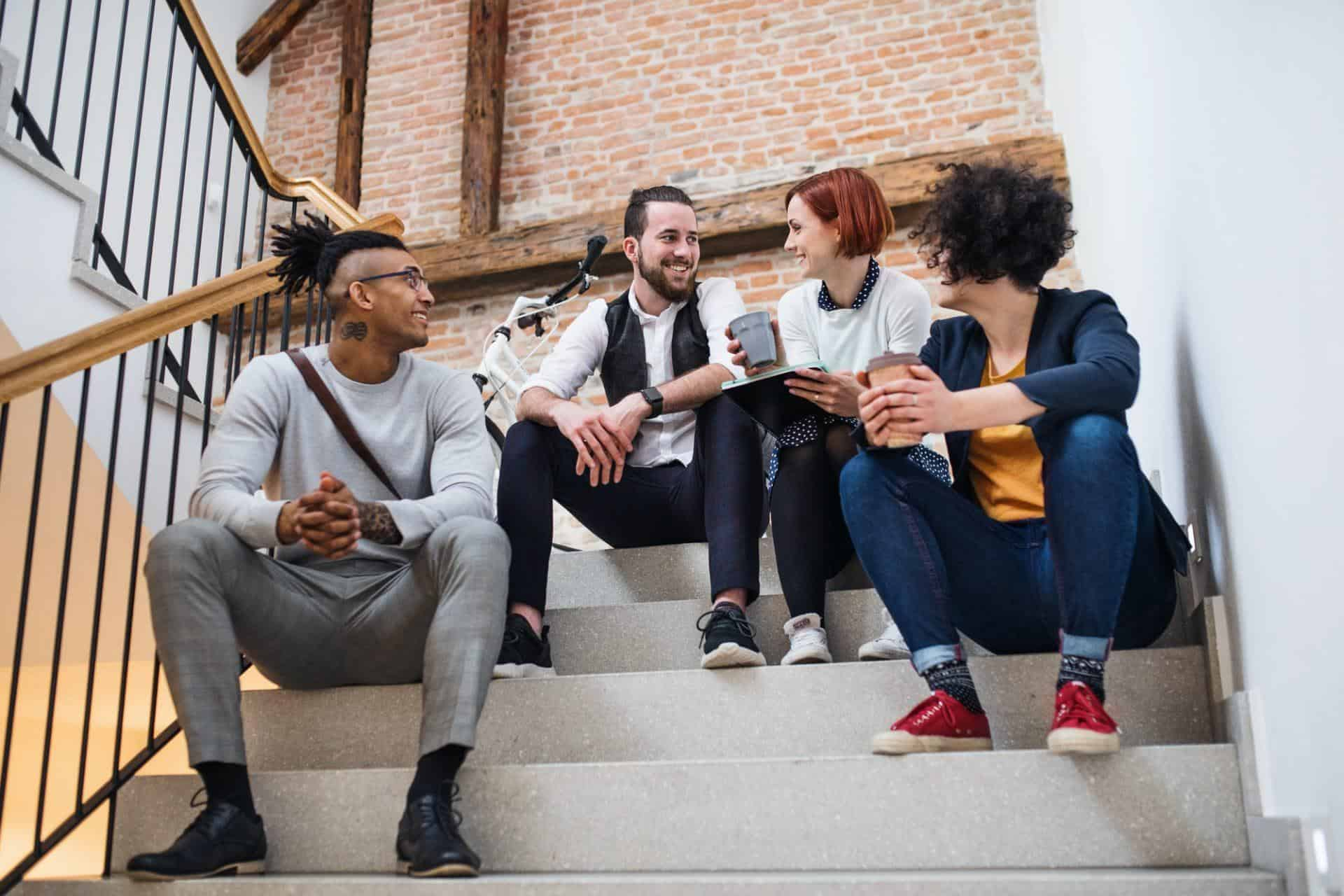 Group of young businesspeople sitting on stairs indoors, talking